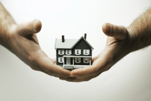 Person holding miniature house.