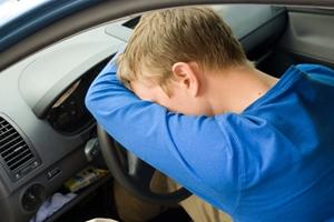 Drunk driver man head on steering wheel